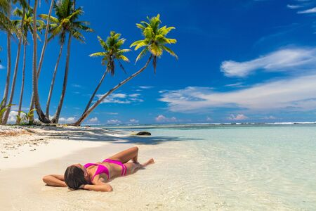 Beach suntan woman relaxing lying down on sand vacation tanning in tropical idyllic summer Caribbean blue sky and palm trees paradise getaway.