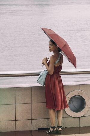 Asian woman walking by river with umbrella under rain during rainy season on summer day vacation. Elegant chinese lady in red dress. Imagens