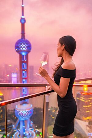 Luxury lifestyle Shanghai city Asian woman drinking white wine glass at rooftop bar party night rich club vip nightclub. Elegant rich lady looking at skyline glowing pearl tv tower in sunset.