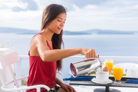 Coffee woman pouring tea in mug for breakfast at hotel room by Mediterranean sea on Europe vacation travel. Happy Asian girl enjoying morning brunch on couple honeymoon.