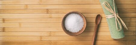 Bath salts spa wellness banner background. Top view of objects on bamboo texture. Exfoliation towel salt in wood bowl and spoon. Panoramic crop.