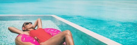Swimming pool suntan woman soaking up the sun sunbathing relaxing on donut float floating on infinity pool panoramic banner. luxury resort vacation sunbathing . Red swimsuit girl happy.