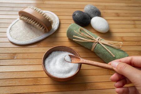 Prodotti per il benessere della spa donna che tiene i sali di epsom da bagno in una ciotola di legno naturale per la cura della salute del corpo della pelle dello scrub dei piedi. Tampone di luffa, spazzolino per unghie, asciugamano esfoliante.