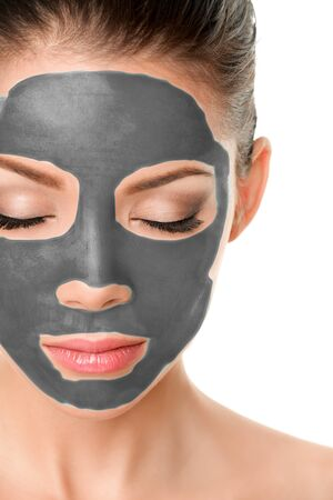 Volcanic clay mask facial treatment asian beauty woman putting mud product on skin for healthy skincare therapy. Stock Photo