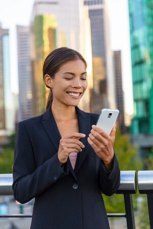 Woman using phone - Asian businesswoman holding smartphone texting on messenger app online to businesspeople. Working outside walking in city street. Happy Chinese Caucasian biracial lady.