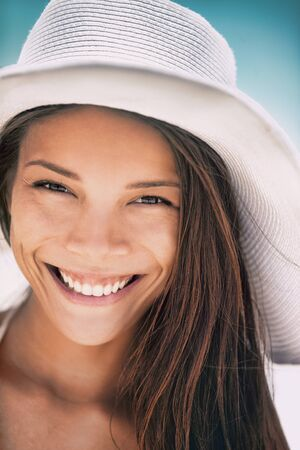 Asian woman smiling happy portrait in summer beach wearing sun hat. Beauty young girl closeup face toothy smile with perfect teeth. 版權商用圖片