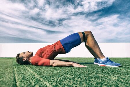 Resistance band training fit man doing bridge exercise fitness athlete doing glute workout outside on grass.