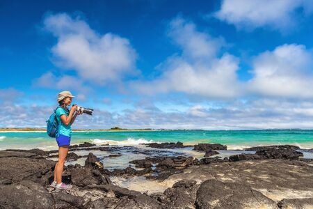 Ecotourism tourist photographer taking wildlife and landscape photos on Galapagos Islands. Woman photographer taking pictures on Isabela island in Puerto Villamil Beach. Marine Iguanas.
