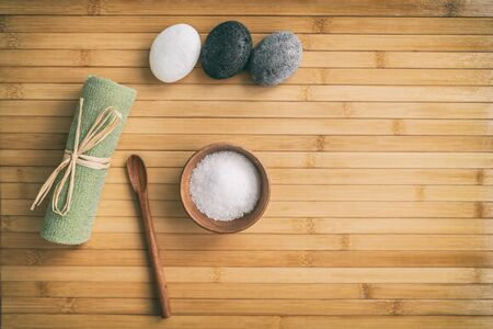 Bath salts natural spa products top view on bamboo wooden texture background with copy space for wellness health concepts. Hot stone massage and exfoliation towel salt in wood bowl.
