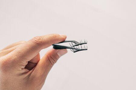 Vista en primera persona de la mujer aplicando pestañas magnéticas falsas con aplicador de metal. Persona sosteniendo pinzas para aplicar imán pestañas postizas tendencia de belleza. Foto de archivo