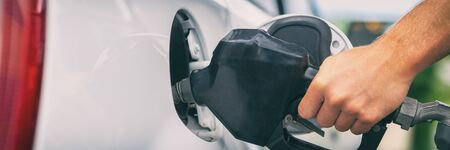 Gas station pump banner panorama. Man filling gasoline fuel in car holding nozzle. Petrol price. Close up. Stockfoto