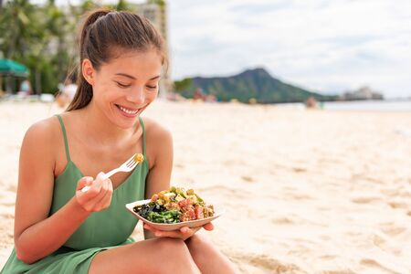 Woman eating poke bowl of ahi tuna on waikiki beach Hawaii. Local food fish salad vacation travel. Asian girl happy healthy eat. Stock Photo