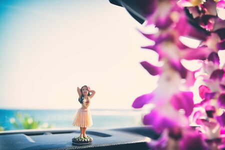Hula doll Hawaii road trip - car hula dancer girl dancing on the dashboard in front of the ocean beach. Tourist vacation and travel holiday concept.