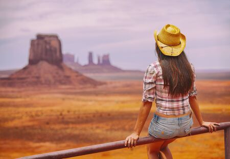 Cowgirl woman enjoying view of Monument Valley in cowboy hat. Beautiful young girl in outdoors, Arizona Utah, USA. Banner panorama. Stock Photo