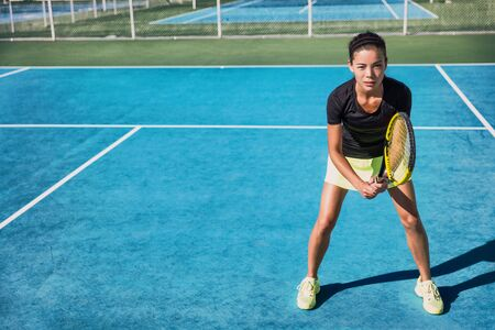 Tennis player woman playing doubles game on blue hard court in outdoor sports club. Asian girl realdy to play. Stok Fotoğraf - 127813804