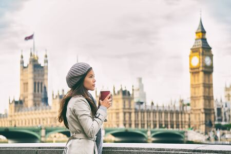 London winter commute lifestyle tourist woman drinking warm tea beverage by Westminster Bridge in morning autumn background. Young professional businesswoman in London, England