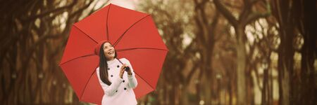 Autumn rain woman walking in park with red umbrella enjoying outdoor forest. Panoramic banner. Asian girl with yellow foliage background. Imagens - 127813812