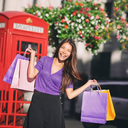 England London shopping woman shopper holding shopping bags by red phone booth. Female shopper smiling in London, England, United Kingdom during spring or summer.