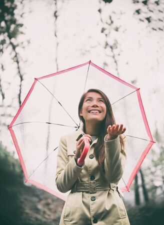 Autumn woman walking in rain with umbrella. Asian model looking up at rainy fall day with hand out and raincoat outside in nature forest. Multiracial Asian girl. Imagens