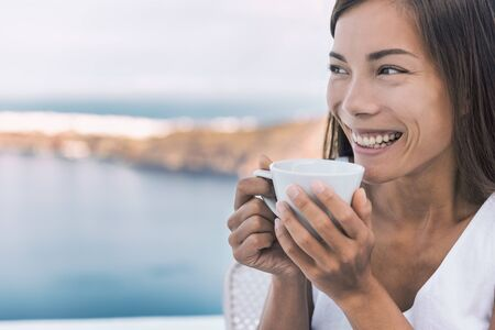 Breakfast coffee girl drinking coffee cup in the morning looking at Mediterranean sea view from hotel or cruise ship balcony. Asian woman relaxing enjoying home lifestyle.