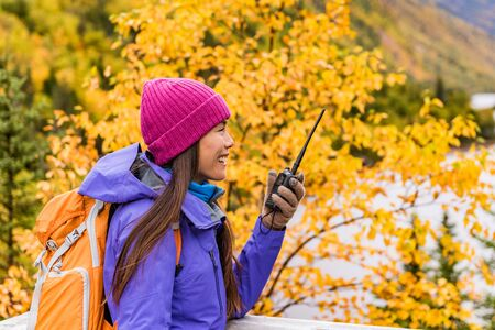 Ham radio gear outdoor hiking girl talking on radio in fall nature with camping equipment. Amateur radio hobby hiker. Stock Photo
