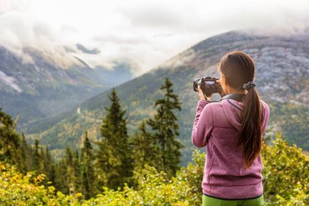 Outdoor travel lifestyle woman photographer shooting video camera at Alaska background. USA vacation holiday in Autumn. Standard-Bild