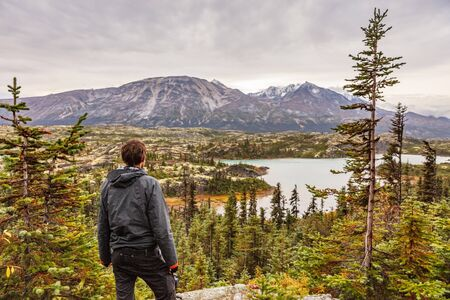 Alaska hiking man travel outdoor lifestyle, Young traveler hiker at mountains landscape in autumn. 免版税图像