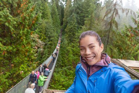 Canada travel tourist woman taking selfie photo at Capilano Suspension Bridge in Vancouver, British Columbia, canadian vacation destination for tourist. Asian girl talking to camera phone. 版權商用圖片 - 128060605