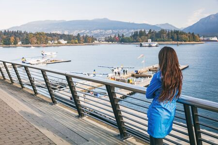 Woman walking in Coal Harbour in Vancouver city in fall, BC, Canada. Autumn travel lifestyle.