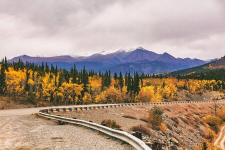 Alaska road trip in Autumn. Highway with mountains in background.