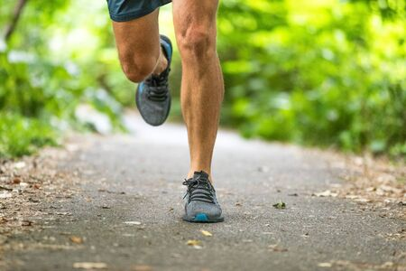 Running man runner athlete workout jogging outdoors on city park path with running shoes closeup of feet and legs. Archivio Fotografico