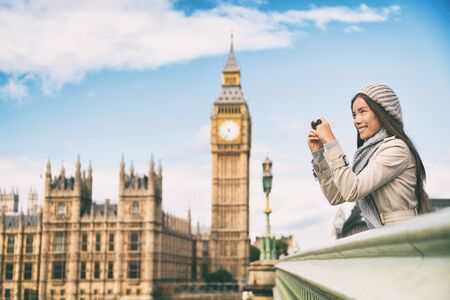 Travel tourist in london sightseeing taking photo pictures near Big Ben. Woman holding smart phone camera smiling happy near Palace of Westminster, Westminster Bridge, London, England Stock Photo