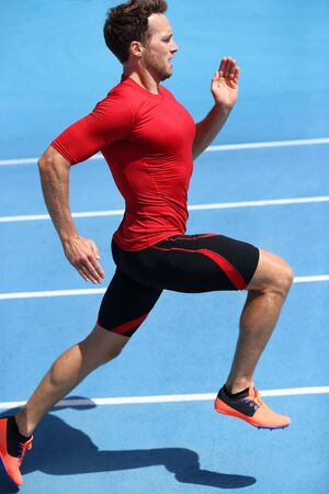 Runner sprinting towards success on run path running athletic track. Goal achievement concept. Male athlete sprinter doing a fast sprint for competition on blue lanes. Track running.
