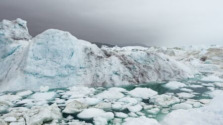 Climate Change and Global Warming - Icebergs from melting glacier in icefjord in Ilulissat, Greenland.
