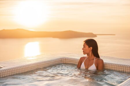 Luxury resort woman swimming in jacuzzi hot tub outside on private hotel room balcony watching sunset over Mediterranean sea. Europe honeymoon vacation.