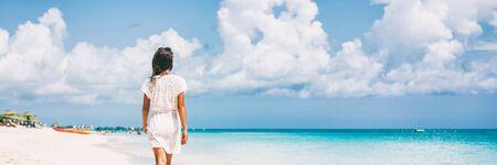Luxuriöse Strandurlaubsreisefrau, die sich auf einem paradiesischen tropischen Urlaubsziel für einen Sonnenurlaub entspannt. Mädchen mit Strandkleid zu Fuß Panorama-Banner.