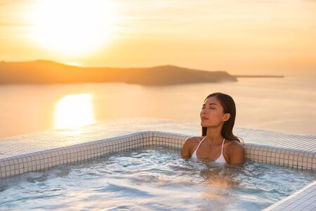 Spa hotel luxury relax jacuzzi therapy pool Asian woman relaxing in resort hot tub outside on private room balcony sunset over sea. Europe honeymoon vacation relaxation wellness pampering.
