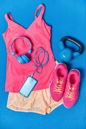 Gym clothes - cute pink activewear outfit - fitness clothing, running shoes, blue headphones and mobile phone for music during training. Fashion style matching tank top, shorts, kettlebell.