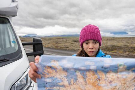 Turista perdido en el viaje por carretera de Islandia buscando direcciones en el mapa de viaje conduciendo autocaravana en vacaciones de aventura en Europa. Mapa de explotación de mujer asiática cara divertida.
