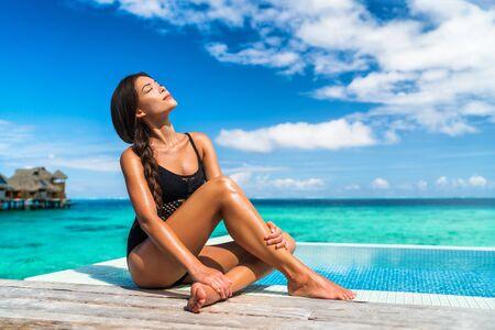 Lusso Bora Bora vacanza hotel donna che prende il sole rilassante nella suite bungalow sull'acqua nella località di Tahiti, destinazione di viaggio della Polinesia francese.