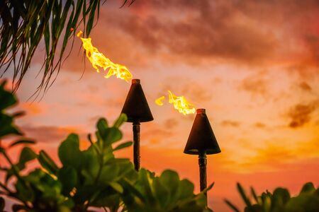 Hawaii luau party Maui fire tiki torches with open flames burning at sunset sky clouds at night. Hawaiian cultural travel vacation background. Stock Photo