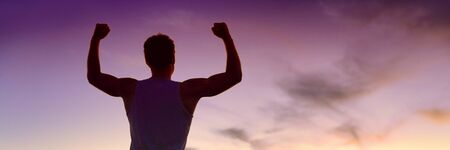 Success life goal achievement strong man flexing muscles at purple dusk sky panoramic banner silhouette of winner athlete happy winning.