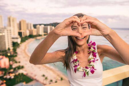 Happy Hawaii Waikiki beach tourist doing heart shape with hands enjoying Honolulu city travel vacation in luxury resort balcony view of sunset. Stock Photo