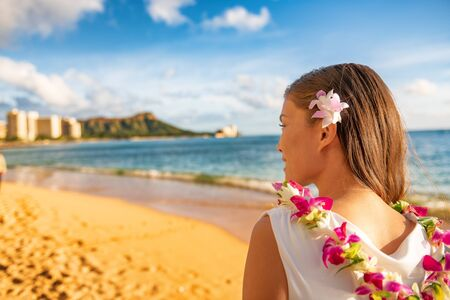 Hawaii woman wearing lei flower necklace and hair accessory on beach sunset for luau party or honeymoon wedding in Waikiki beach, Honolulu, holiday travel. Stock Photo