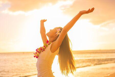 Hawaii ballerina di hula donna che indossa collana di fiori lei sulla spiaggia al tramonto ballando a braccia aperte libere al tramonto rilassandosi durante le vacanze di viaggio hawaiane. Ragazza asiatica con i capelli di fiori freschi, danza tradizionale.