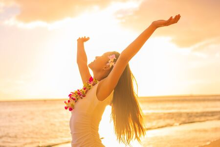 Mujer de bailarina de hula de Hawaii con collar de flores lei en la playa al atardecer bailando con los brazos abiertos libres en la puesta de sol relajante en vacaciones de viaje hawaiano. Chica asiática con pelo de flores frescas, danza tradicional.
