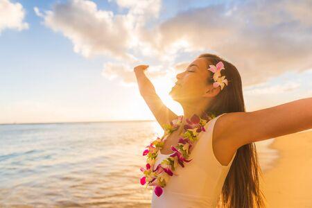 Hawaii hula luau woman wearing hawaiian lei flower necklace on Waikiki beach dancing with open arms free on hawaiian vacation. Asian girl with fresh flowers hair, traditional polynesian dance.