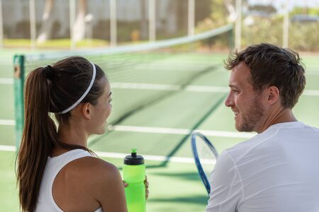 Tennis players mixed doubles talking after match on hard court outside at tennis club. Private teacher man giving lesson to Asian woman or couple having fun.