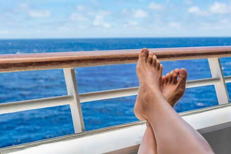 Cruise vacation travel woman relaxing with feet on balcony ship deck enjoying ocean view of holiday destination. Closeup of legs and boat railing.