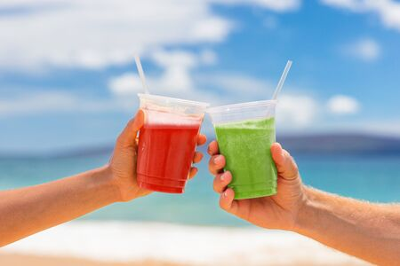 Healthy juice smoothie drinking couple toasting cold pressed organic drinks together at beach restaurant. Detox smoothie drink toast at summer vacations holidays. Fruit juicing weight loss diet. Banco de Imagens - 129312381